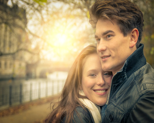 Couple in love - Beautiful woman hugging her man and smiling at sunset - Autumn and winter mood
